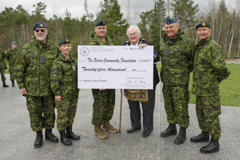 Grand Master John Green (third from the right) presenting Base Commander Colonel Liam McGarry (fourth from the right) with a cheque for the Borden Legacy Project at the Borden Legacy Wall, Canadian Forces Base (CFB) Borden, Ontario on May 2, 2017.                                                                                      Also present: Honorary Colonel John Williams, Chief Warrant Officer Crystal Harris, Honorary Colonel Jamie Massie, and Honorary Colonel Barrie Peacock.                                                                            Photo: Avr Rachael Allen, CFB Borden Imagery                                                     CB06-2017-0198-016